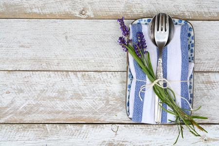 servilletas: cubiertos de plata en una servilleta blanca azul con decoración de lavanda y copyspace vacío en estilo rústico de la vendimia Foto de archivo
