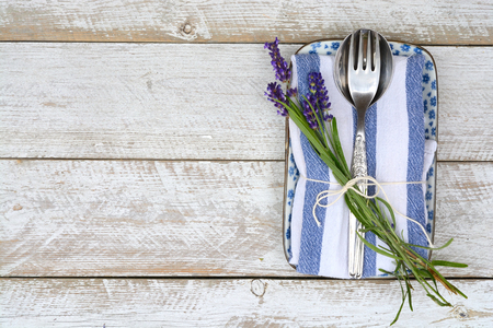 silver cutlery on a blue white napkin with lavender decoration and empty copyspace in vintage country style