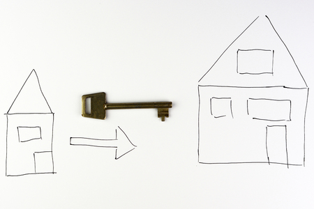 prefabricated: drawing of a house with arrow and key on a white background symbol of moving to another house with an empty copyspace Stock Photo
