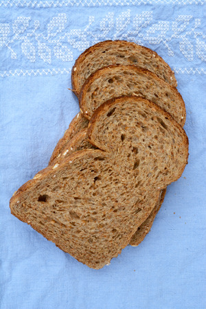 wheat flour: Healthy fresh wholewheat slice of bread on a blue tablecloth Stock Photo