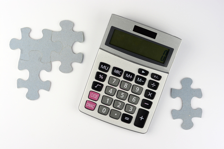 Calculator on a white gray background with question mark and puzzle pieces with copyspace for finance administration 스톡 콘텐츠