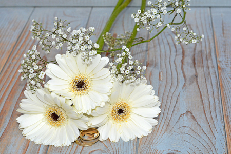 daisys: White gerber daisys with wedding rings on a old empty copyspace background of wooden shelves Stock Photo