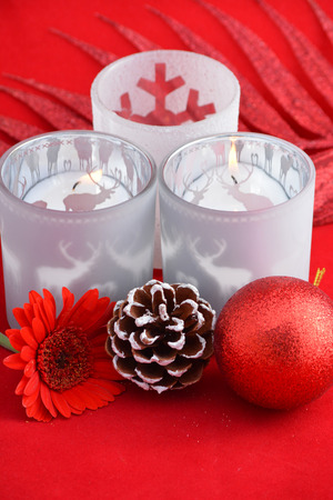 pine three: Christmas background with three red tea candle holders decorated with a wooden reindeer, pine apple and christmas ball