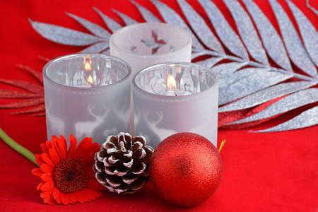 pine three: Christmas background with three red tea candle holders decorated with a glitter twig, pine apple and christmas ball