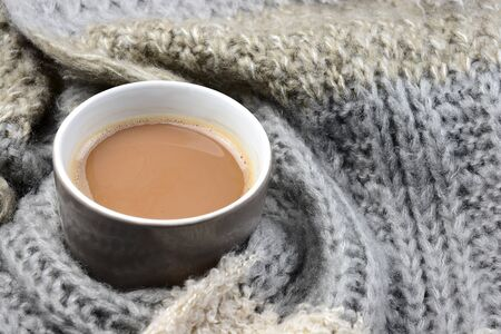ecru: Hot chocolate in cup coffee mug with a gray, ivory, ecru knitted scarf blanked wrapped around it and chocolate bar Stock Photo
