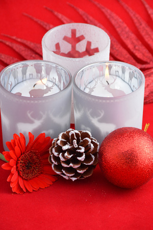 red gerber daisy: Christmas background with three red tea candle holders decorated with red gerber daisy, pine cone and christmas ball