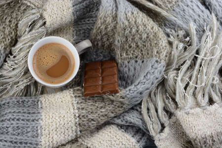 fringes: Hot chocolate in cup coffee mug with a gray, ivory, ecru knitted scarf blanked wrapped around it and chocolate bar Stock Photo