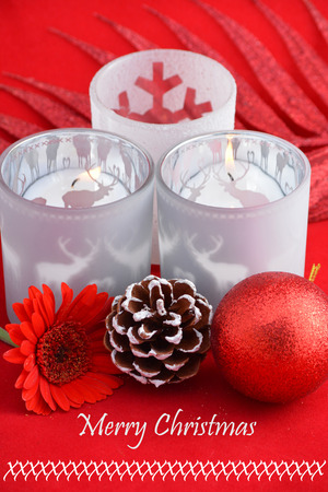 pine three: Christmas background with three red tea candle holders decorated with a gerber daisy pine apple and christmas ball and merry christmas text Stock Photo