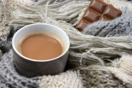 blanked: Hot chocolate in cup coffee mug with a gray, ivory, ecru knitted scarf blanked wrapped around it and chocolate bar Stock Photo