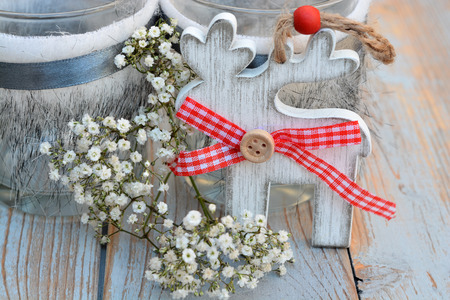 wooden reindeer: Old wooden shelves gray with red white Christmas decoration zoals wooden reindeer and candles holder decorated with babys breath flowers