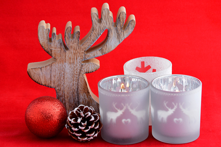 wooden reindeer: Christmas background with three red tea candle holders decorated with a wooden reindeer, pine apple and christmas ball