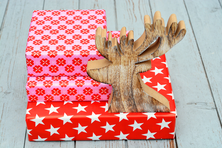 wooden reindeer: Red and pink star flower pattern christmas gifts with wooden reindeer on a wooden shelves background