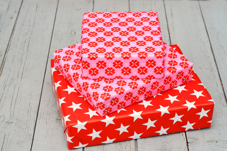 three gift boxes: Red and pink star flower pattern christmas gifts on a wooden shelves empty copyspace background surface