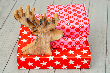 wooden reindeer: Red and pink star flower pattern christmas gifts with wooden reindeer on a wooden shelves background with copy space