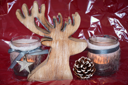 wooden reindeer: red shiny glitter christmas background with gray wooden reindeer decoration and tea candle lights