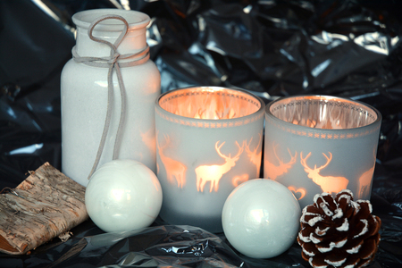 tea candle: black shiny glitter christmas background with gray christmas decoration and reindeer tea candle lights Stock Photo