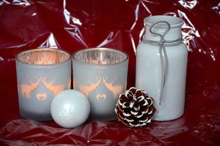 tea candle: red shiny glitter christmas background with gray christmas decoration and reindeer tea candle lights Stock Photo