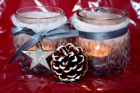 pine three: Christmas background with three red tea candle holders decorated with a fur and ribbon, pine cone and christmas ball