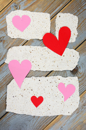 handmade paper: Wooden shelves table Background with handmade paper notes recylcled decorated with pink and red hearts for wedding invitation and Valentines day card Stock Photo