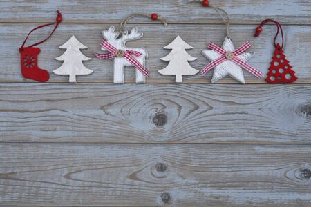 christmas tree decoration: White red christmas decoration as Christmas tree, reindeer and star on a gray old wooden planks background whith empty copyspace