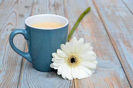 Vintage blue coffee cup on a old wooden table background with a white daisy flower