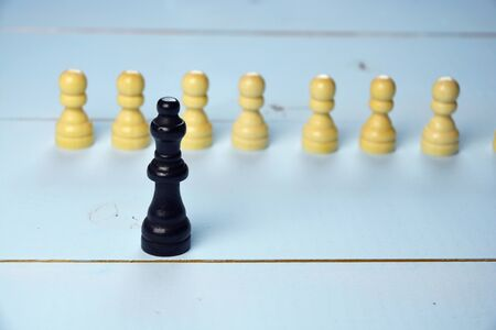 Abstract business concept with King chess piece, the boss standing out of the crowd, employees on a blue wooden background Stock Photo