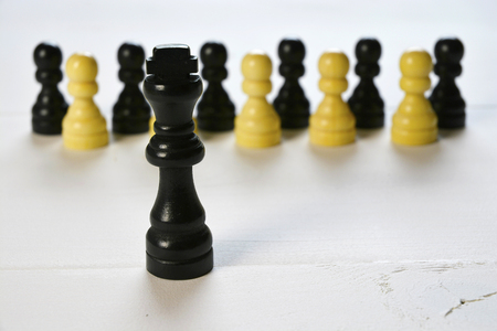 Abstract business concept with king chess piece, the boss standing out of the crowd, employees on a white wooden background