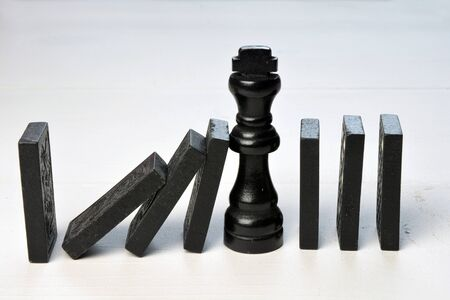 Abstract business concept with king chess piece and domino pieces fallen on a white wooden background