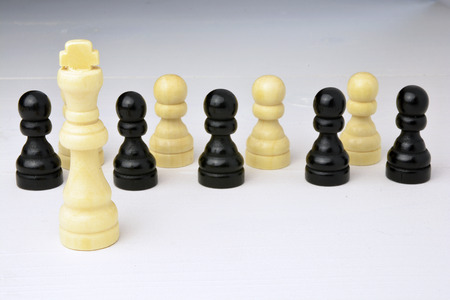 select: Abstract business concept with king chess piece, the boss standing out of the crowd, employees on a white wooden background