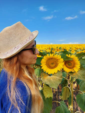 A beautiful young blonde woman in a blue T-shirt, wearing hat, enjoy nature in the sunflower field at sunrise. Фото со стока