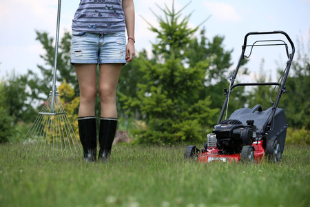Young woman cutting the lawn with motorized mower photo