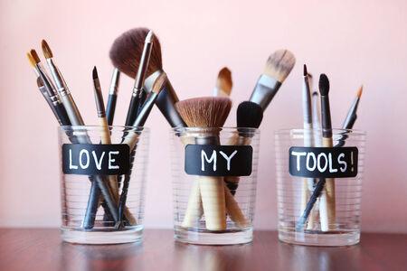 faire l amour: Pinceaux de maquillage dans des bocaux en verre - aimer mes outils Banque d'images