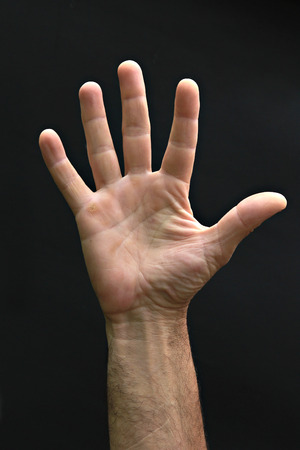 Mans hand showing five fingers on the black photo