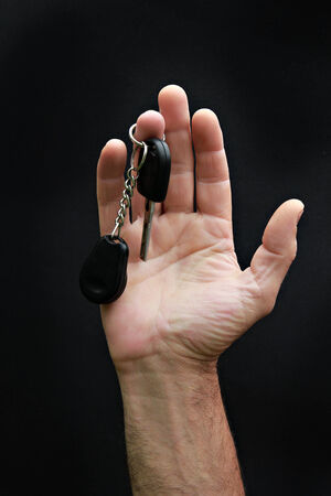 Mans hand holding car key on the black photo