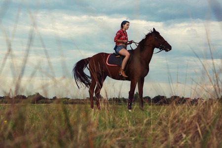 Young woman with red plaid shirt riding horse outdoor Stok Fotoğraf