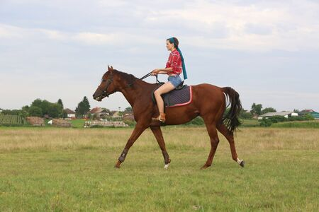 red plaid: Young woman with red plaid shirt riding horse outdoor Stock Photo