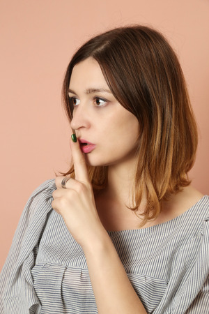 shushing: Young woman with finger on his lips asking for silence