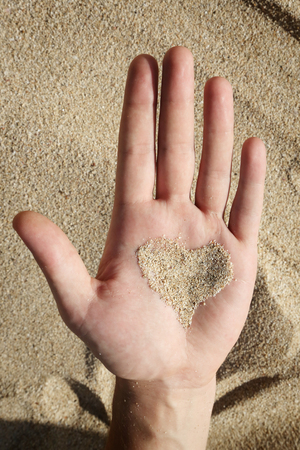 anniversary beach: Heart shaped sand on mans palm