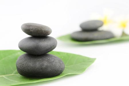 white stones: Balanced black zen stones on white background Stock Photo