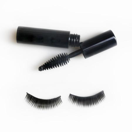 fake eyelashes: False lashes and black mascara isolated on white Stock Photo
