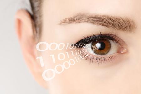 ojos marrones: Primer plano del ojo de la mujer con el código binario Foto de archivo