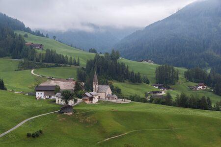 Landschaften mit Kirche San Giovanni und kleinem Dorf im Val di Funes, Dolomiten, Südtirol, Italien, Europa