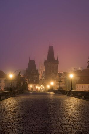 Landscapes on Charles Bridge with Bridge Tower and Statues at sunrise in a foggy morning, Prague, Czech Republic, Europe