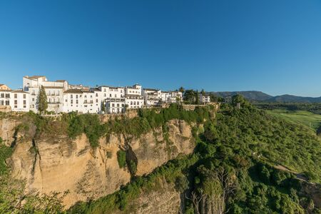 Ronda aldea en el borde del acantilado con árboles y casas blancas contra el cielo, Andalucía, España