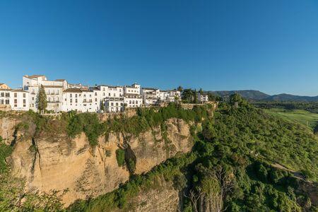 Ronda Dorf am Rande der Klippe mit Bäumen und weißen Häusern gegen Himmel, Andalusien, Spanien