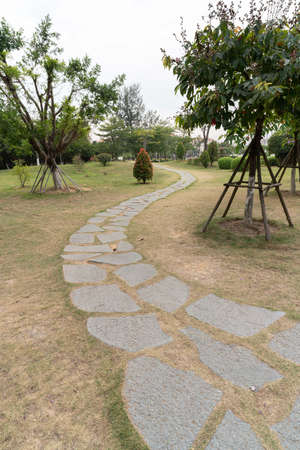 Small stone road on the grassland in a public park in cloudy day Stock fotó