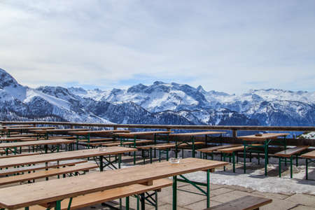 Outdoor restaurant terrace on top of snow mountain, with wooden tables in foreground and Jenner mountain in distance Bavaria, Germany