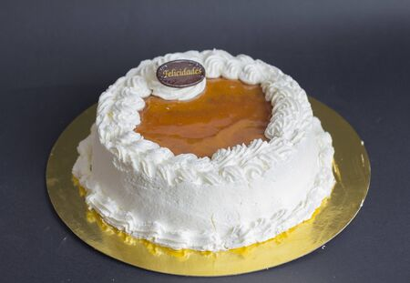 white cream cake on gold plate with back background. San marcos cake. Felicidades signal.