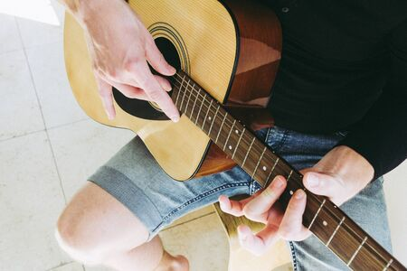 Guy playing on acoustic guitar