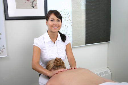 Massage therapist giving neck and shoulder massage Stock Photo